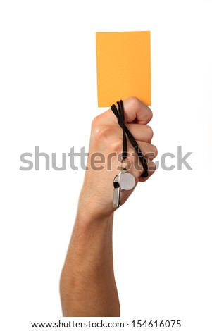 Human Hand with whistle, yellow card, Isolated on white background. - stock photo