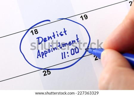 """Human hand writes reminder """"Dentist appointment 11-00"""" in calendar.  - stock photo"""