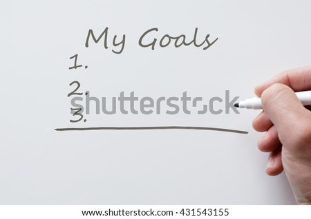 Human hand writing my goals on whiteboard
