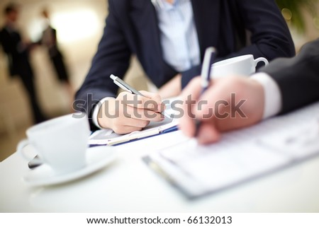 Human hand writing on paper in working environment - stock photo