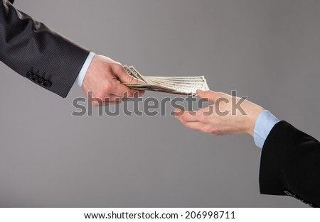Human hands accepting an offer of money on grey background - stock photo