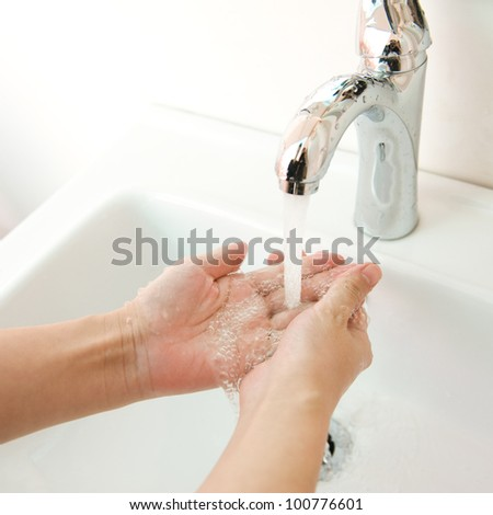 human hands being washed under stream of pure water from tap - stock photo