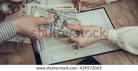Human hands exchanging money above business graph. toned image - stock photo