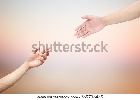 Human hands help together on blur dream sunset sky backgrounds.faith and belief of religious conceptual:support and kindness of friendship:forgiveness and blessing conception.love/heal/treat of god - stock photo