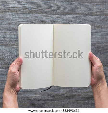 Human hands holding blank open book, catalog, magazines, brochure, note template with paper texture on wood floor background: Empty textured note pocketbook pages document mockup template top view  - stock photo