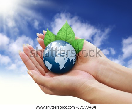 human hands holding blue earth with a leaf on sky background