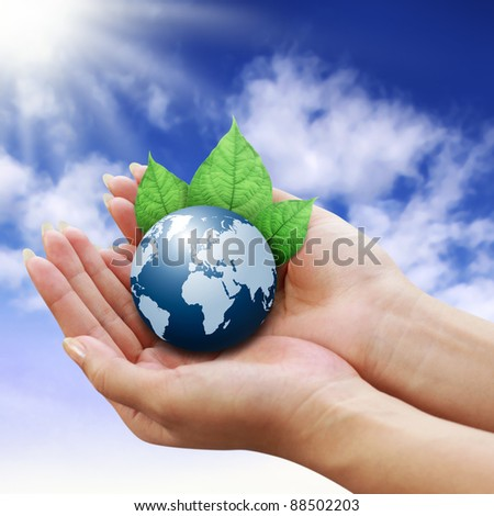 human hands holding blue earth with a leaf on sky background - stock photo