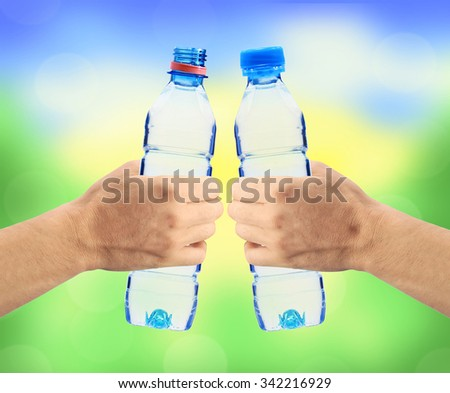 Human hands holding bottles of water on the nature background - stock photo