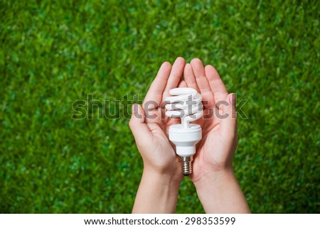 Human hands holding energy saving lamp close up