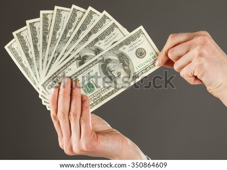 Human hands holding fan of dollars, closeup shot on dark background
