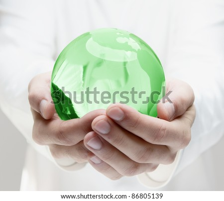 Human hands holding glass earth - stock photo
