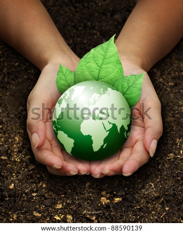human hands holding green earth with a leaf on Fertilizer soil background - stock photo