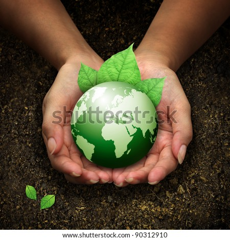 human hands holding green earth with a leaf on soil - stock photo