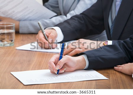 Human hands holding pens and papers, making notes in documents on the table with glasses of water on it