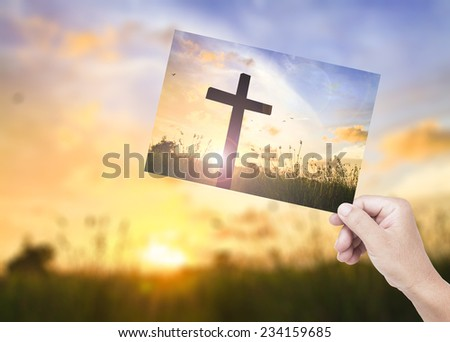 Human hands holding picture the cross over a sunset background compare with the actual location. - stock photo