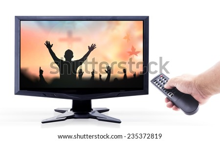 Human hands holding remote and monitor display silhouette people raising hands over blurred crown of thorns and the cross on white background. - stock photo