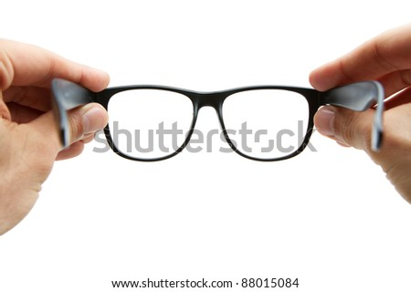 Human hands holding retro style eyeglasses - stock photo