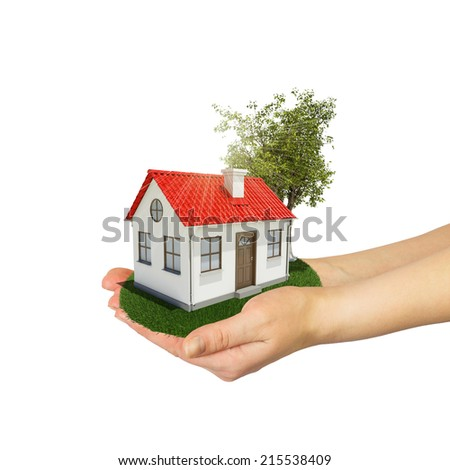 Human hands holding small house with tree and grass - stock photo