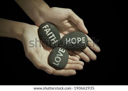 Human hands holding stones with religious text - stock photo