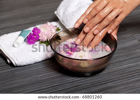 Human hands in bowl with cosmetic oil and chrysanthemum flowers. Beauty treatment in spa salon - stock photo