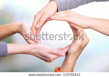 Human hands making circle on bright background - stock photo