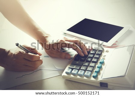 Human hands on using calculator and tablet on finance data chart paper - with copy space on screen