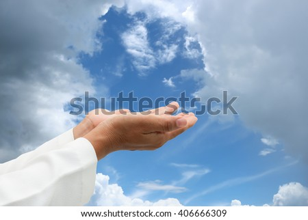 Human Hands praying on sky background. - stock photo