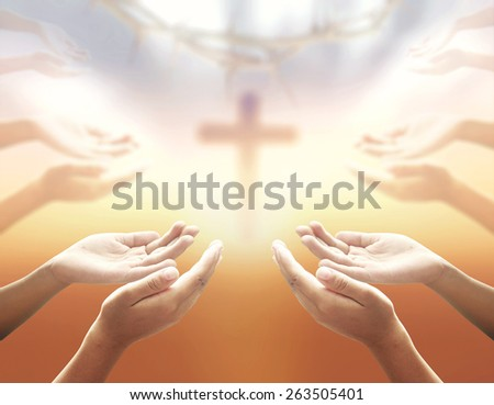 Human hands praying over blurred crown of thorns and the cross on a sunset. - stock photo