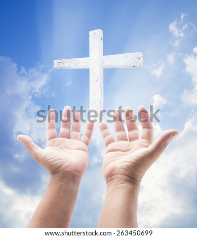 Human hands praying over the white cross and amazing light background. - stock photo