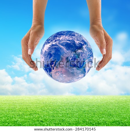 Human hands protect global Earth over gas clouds and Sun over green glass a World Environment Day Concept Elements of this image furnished by NASA - stock photo