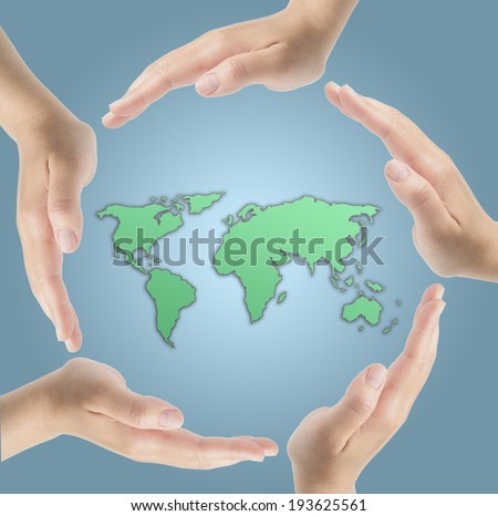 Human hands surrounding the Earth  - stock photo