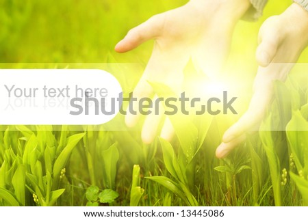 Human hands touching green grass. Graphic design elements on it are perfect to put text on - stock photo