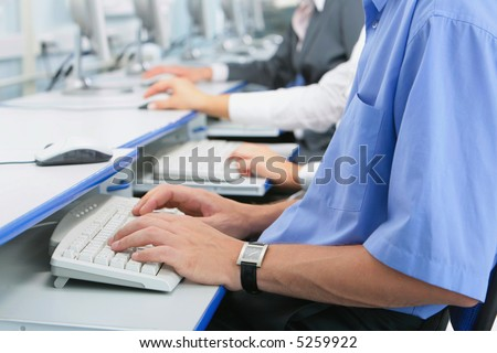 Human hands typing on the keyboard in the computer room - stock photo
