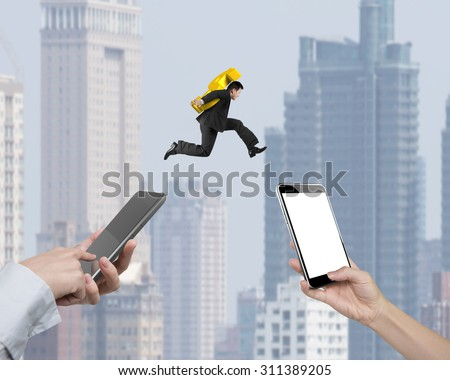 Human hands using different smart phones to transfer money, with businessman carrying dollar sign jumping, electronic trading concept. - stock photo