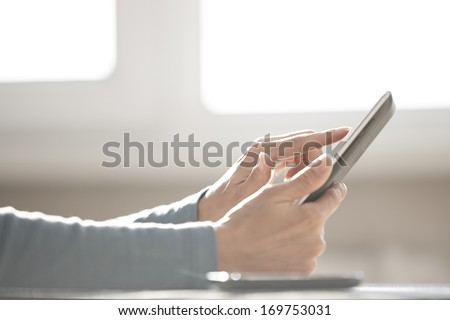 Human hands using tablet computer at home