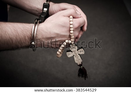 Human Hands with a crucifix handcuffed
