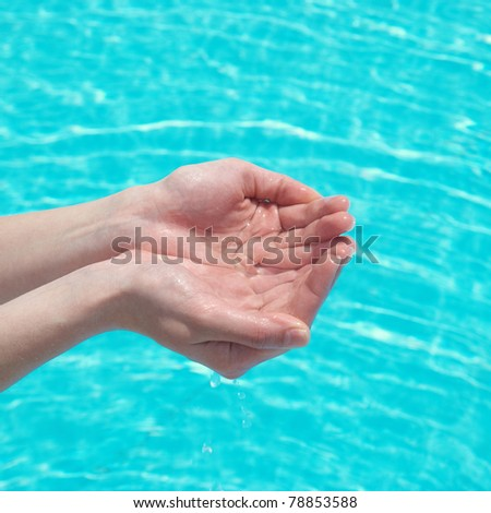 Human hands with clear water on the blue background - stock photo