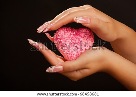 Human hands with long acrylic fingernail and beautiful manicure holding pink heart. Over black - stock photo