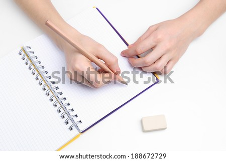 Human hands with pencil and erase rubber and notebook, isolated on white - stock photo