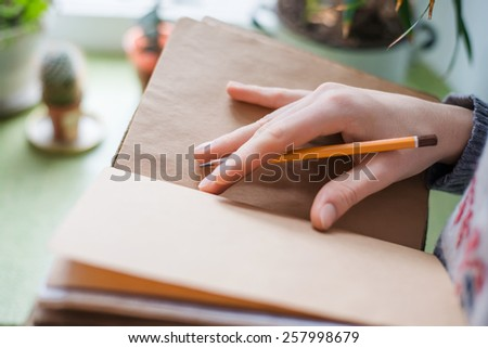 Human hands with pencil writing on paper