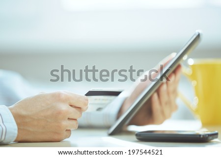 Human hands with tablet PC and credit card during lunch - stock photo