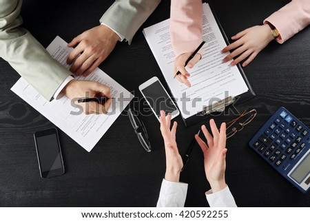 Human hands working with documents at the desk, top view