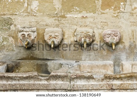 Human head fountain. Ancient stone fountain with four faces with metal pipe in the mouth