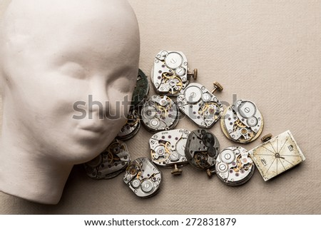 Human head made of clay lying over clock mechanisms and dials.  time goes by, running out of time,  time flies . - stock photo