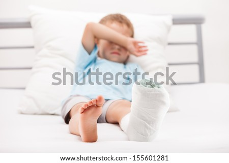 Human healthcare and medicine concept - little child boy with plaster bandage on leg heel fracture or broken foot bone - stock photo
