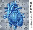Human heart symbol on a jigsaw puzzle representing clinical hospital research for medical cardiovascular blood circulation condition that results in a heart attack or stroke. - stock photo