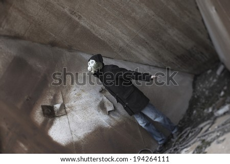 Human in gas mask standing at the industrial place - stock photo