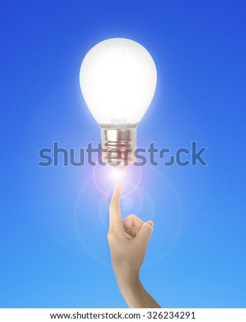 Human index finger pointing at lightbulb with bright light, on blue background. - stock photo