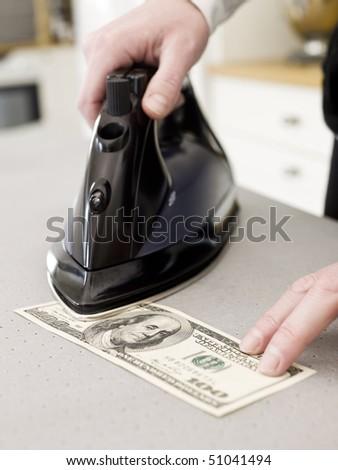 Human ironing a Hundred dollar bank note - stock photo