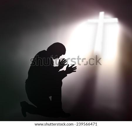 Human kneeling and raising hands over the cross. - stock photo
